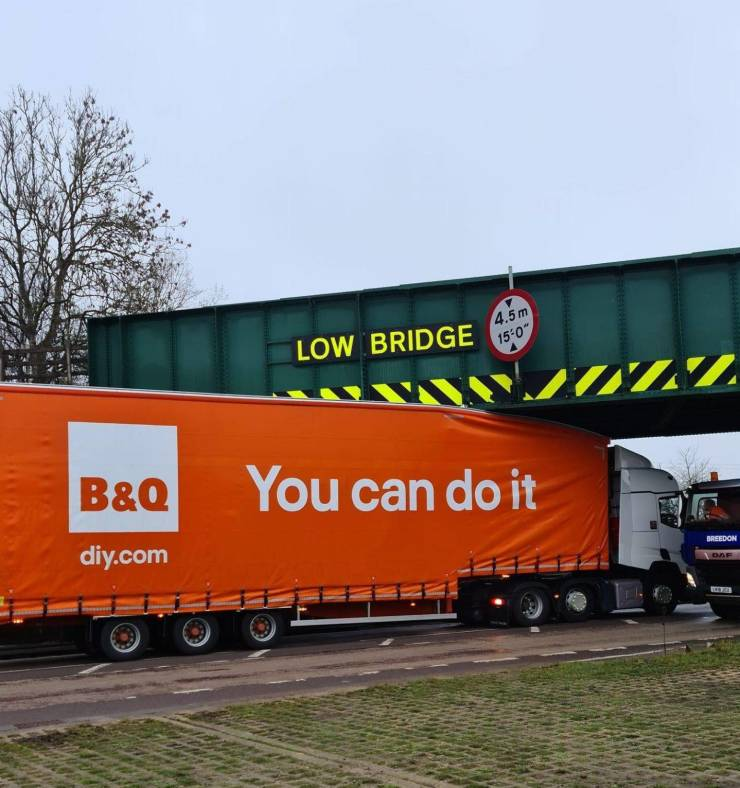 "A truck labeled ""You can do it"" crashed into a bridge that reads ""Low bridge""."