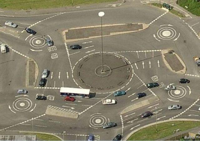 Imagen caótica de una glorieta de coches con cuadro rotondas en cada esquina