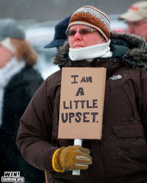 Hombre en una manifestación con un cartel que dice Estoy un poco molesto