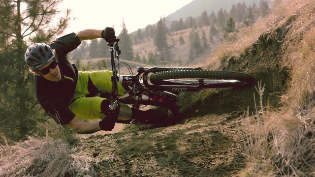 Mountain Biker Takes a Sharp Turn in parallel to the Ground