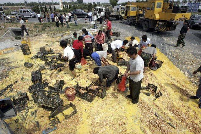 Chinese People Scavenge Goods from an Overturned Trucks