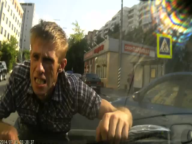 Crazy Man in Russia Jumps on Woman's Car  (VIDEO)