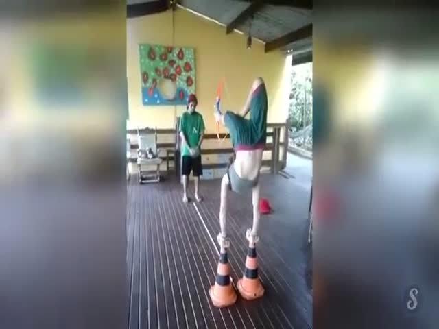 Woman Shoots a Bow with Her Feet While Balancing on Traffic Cones