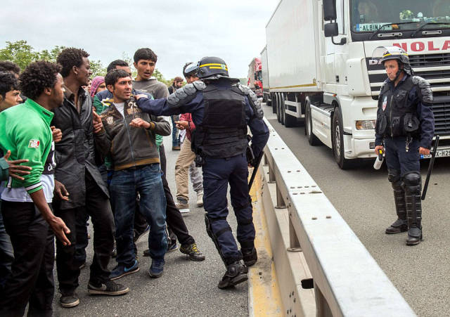 Riot Police Try to Stop Hundreds of Migrants from Crossing into the UK