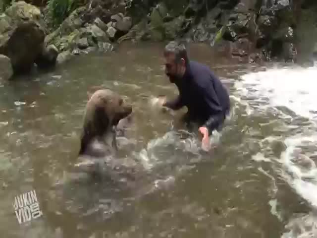 Man and a Bear Have a Friendly Water Fight in the Wild