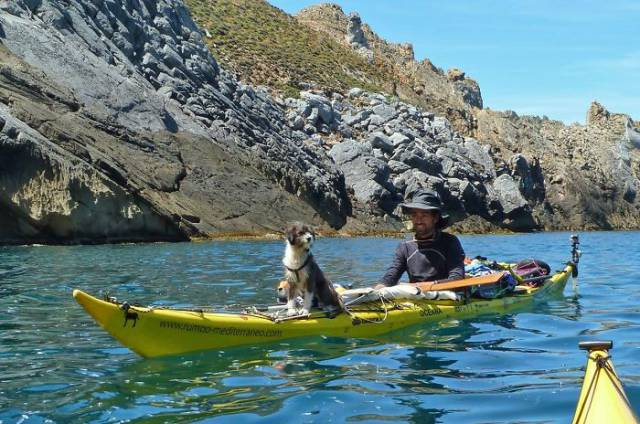 Man Kayaking The Sea With A Dog He Found On The Way